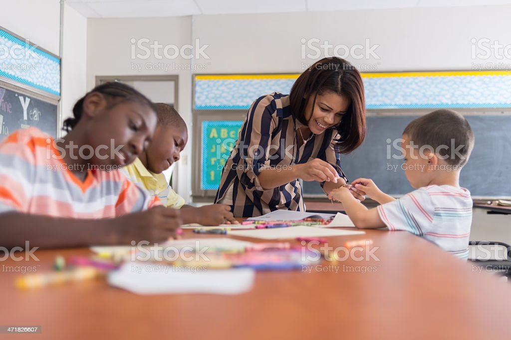 Woman helping a student at art in an inner city school stock photo