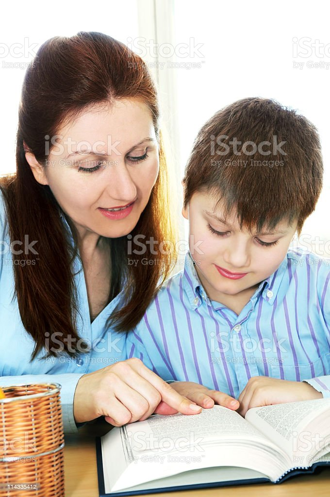 Woman helping child read from a book on a desk royalty-free stock photo