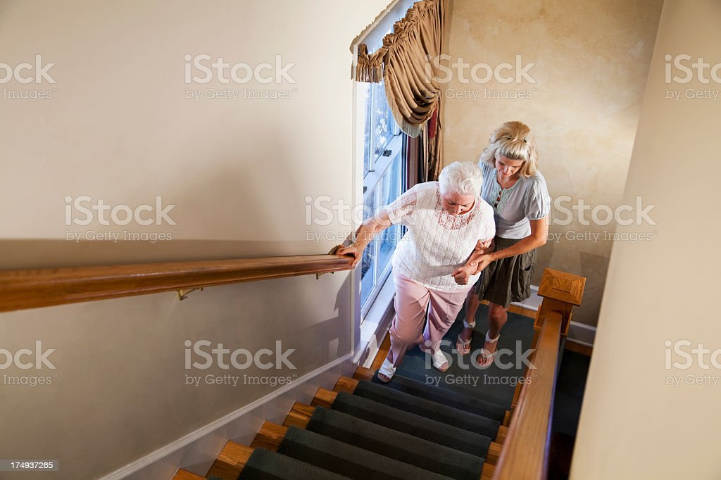 Woman helping grandmother climb stairs stock photo