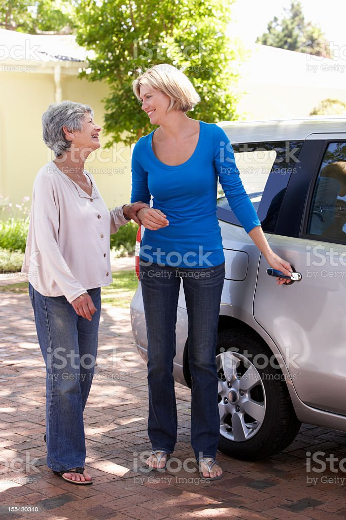 Woman Helping Senior Lady Into Car stock photo