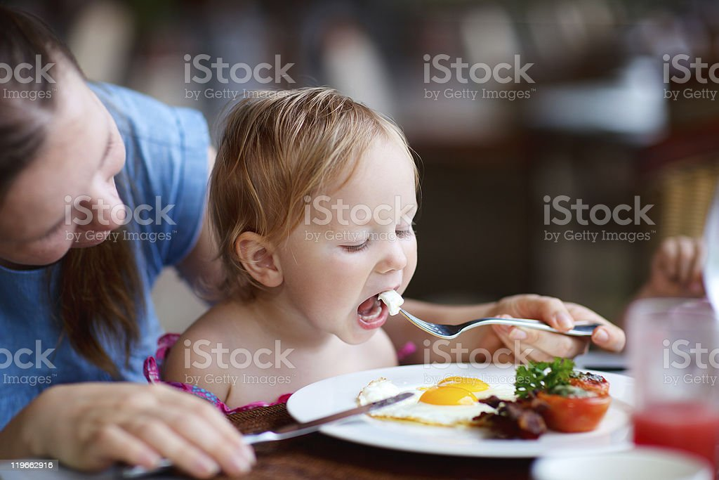 Woman helping small child eat fried eggs at table stock photo