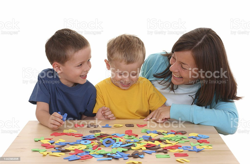 Woman helping two boys with their letters royalty-free stock photo