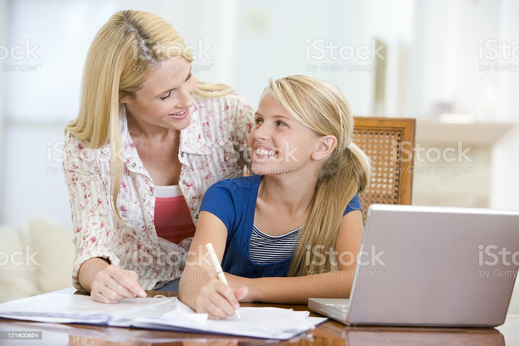 Woman helping young girl do homework in dining room stock photo