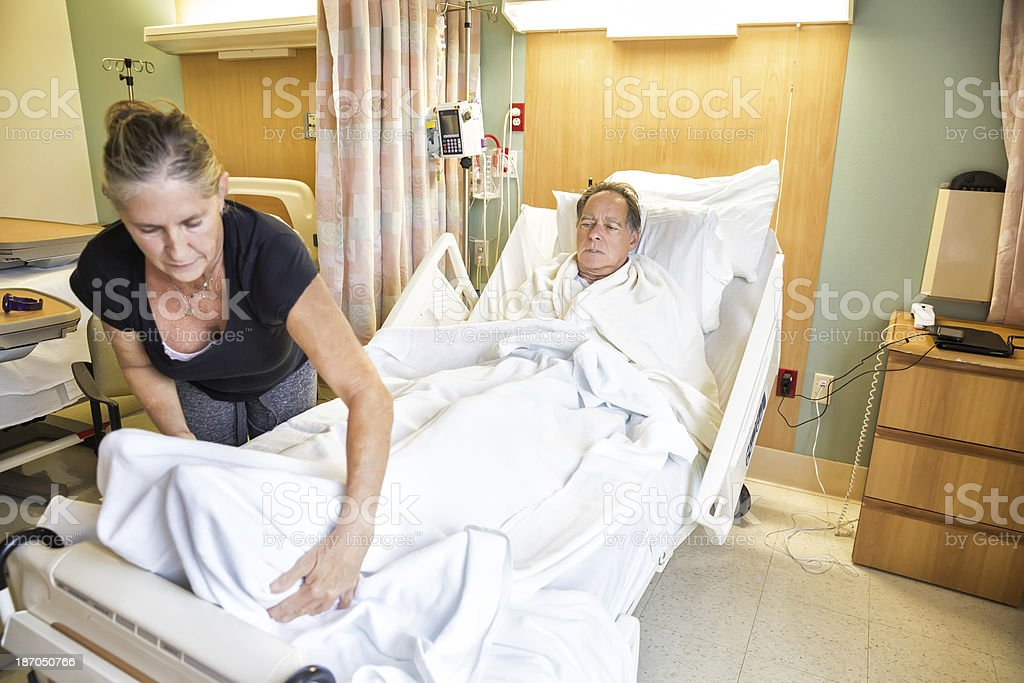 Woman helps her husband get comfortable in the hospital royalty-free stock photo