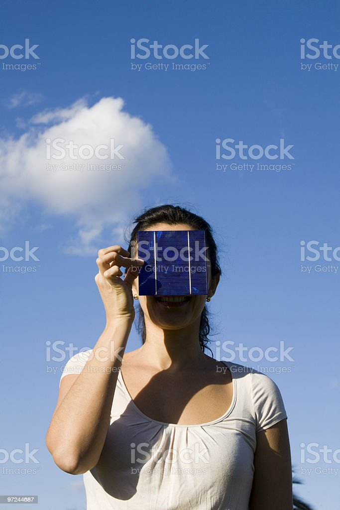 Woman hides behind a solar cell royalty-free stock photo