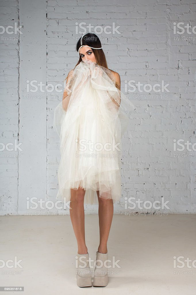 Woman hides her face behind skirt tutu stock photo