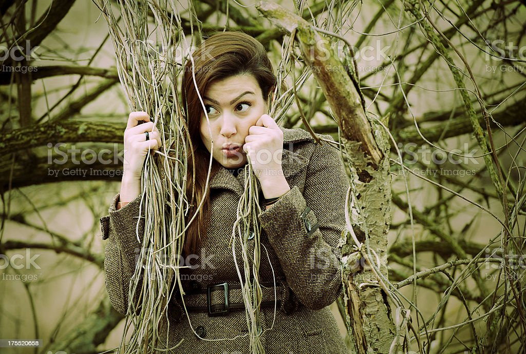 Woman hiding behid branches royalty-free stock photo