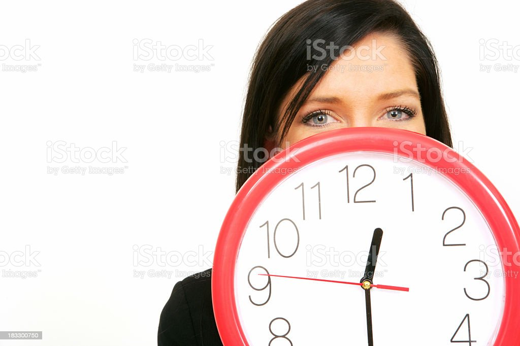 A woman hiding behind a red wall clock stock photo