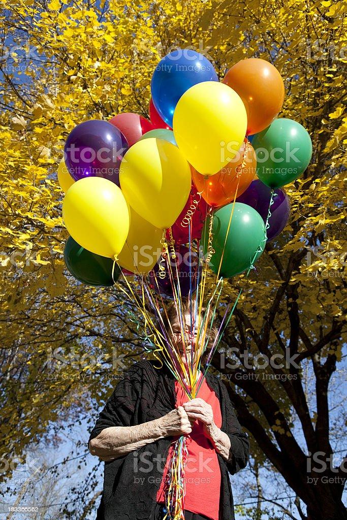 Woman Hiding Behind Balloons stock photo