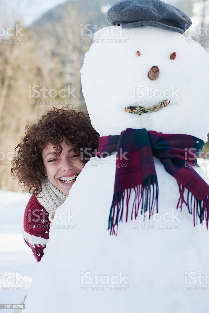 Woman hiding behind snowman royalty-free stock photo