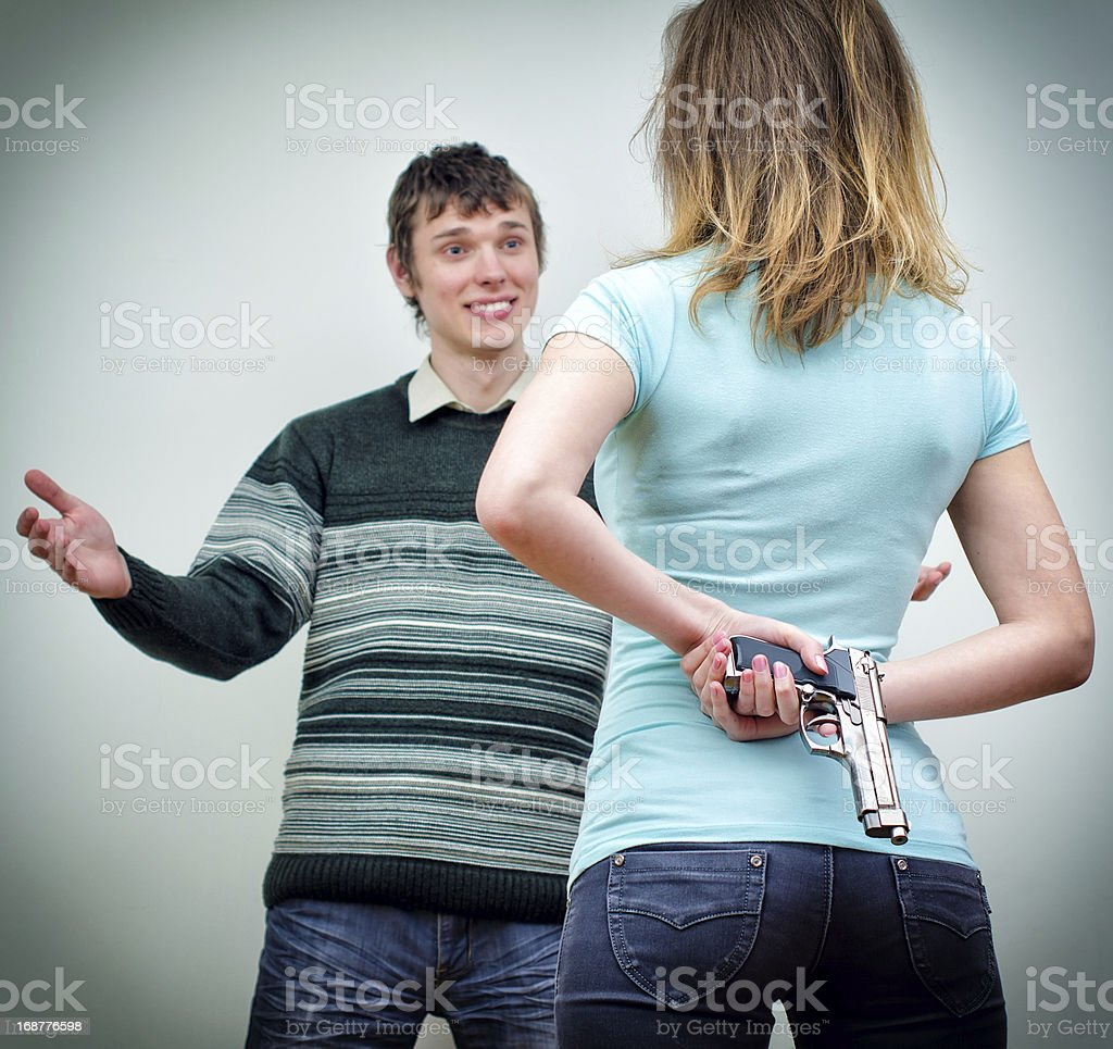 Woman hiding gun underhand talking to man stock photo
