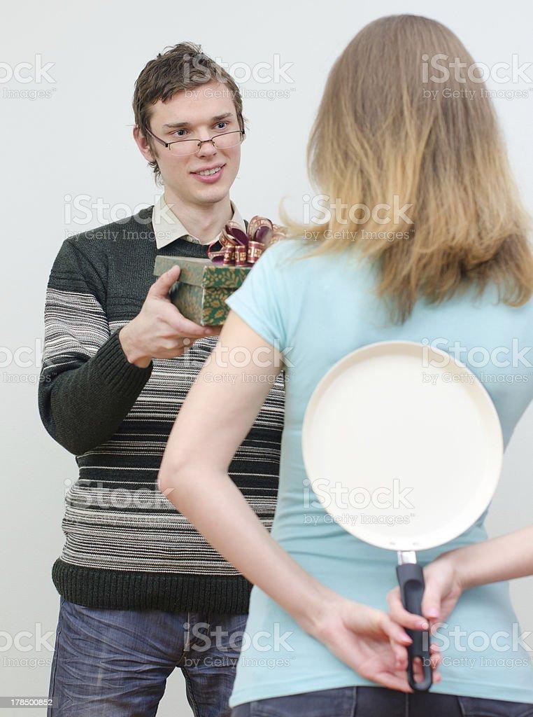 Woman hiding pan underhand talking to man stock photo