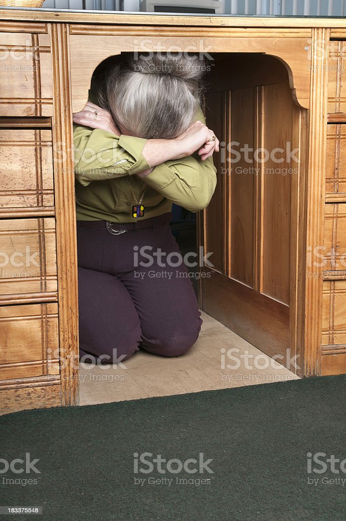 Woman Hiding under a Desk stock photo