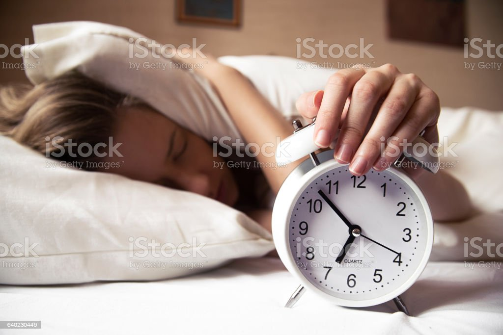 Woman hiding under pillow upon waking up with alarm clock stock photo