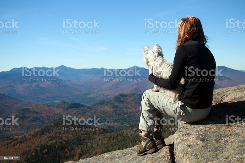 Woman hiking and holding westie dog on a mountain summit stock photo