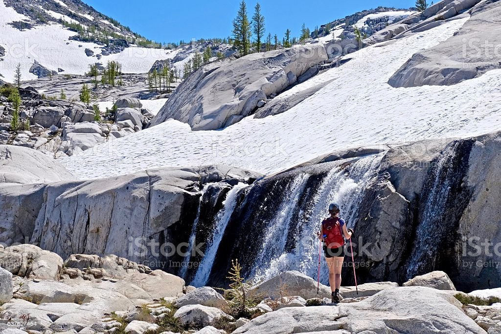 Woman hiker by waterfalls. stock photo
