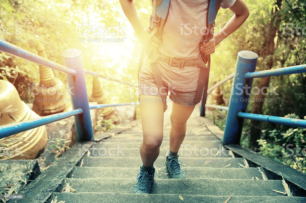 Woman hiker climbing stone steps on a mountain in sunshine stock photo