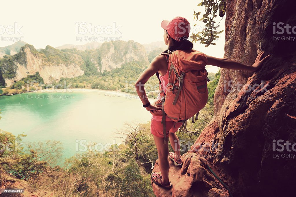 woman hiker enjoy the view at sunrise mountain peak cliff stock photo