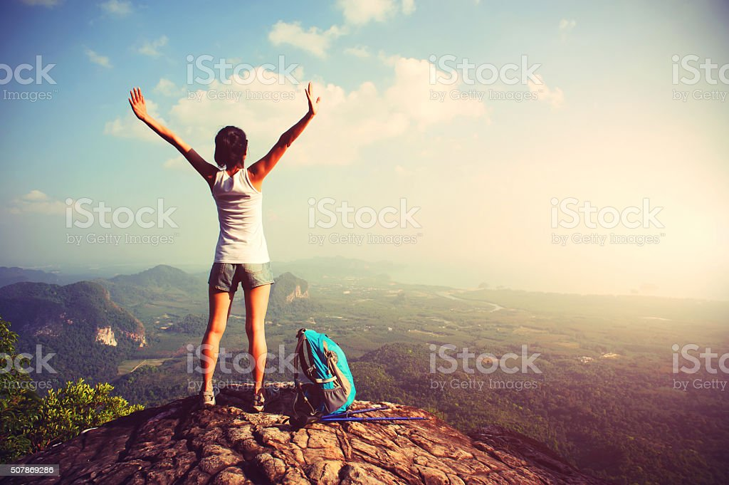 woman hiker enjoy the view on mountain peak cliff stock photo