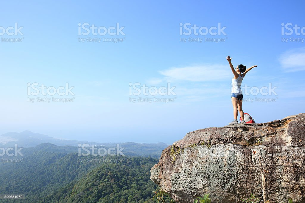 woman hiker enjoy the view on mountain peak cliff stock photo