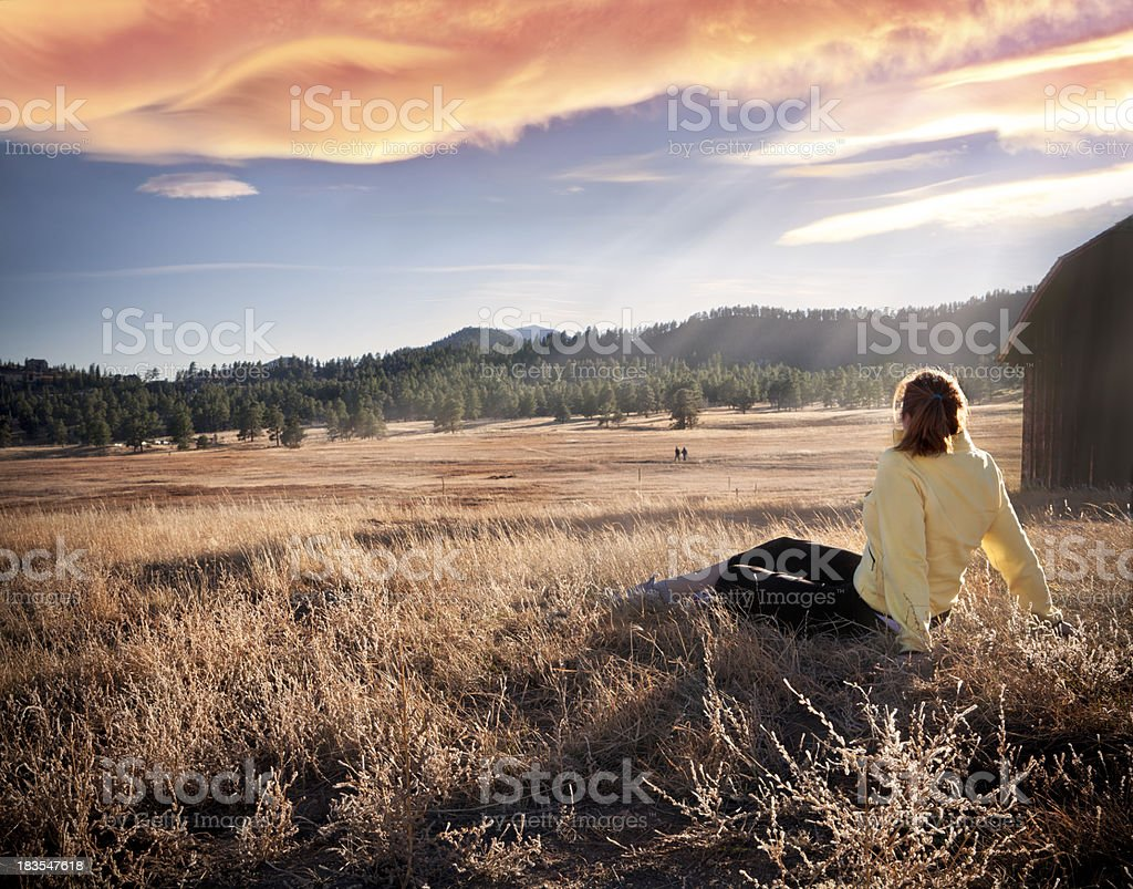 Woman Hiker Relaxing in Meadow at Sunset royalty-free stock photo
