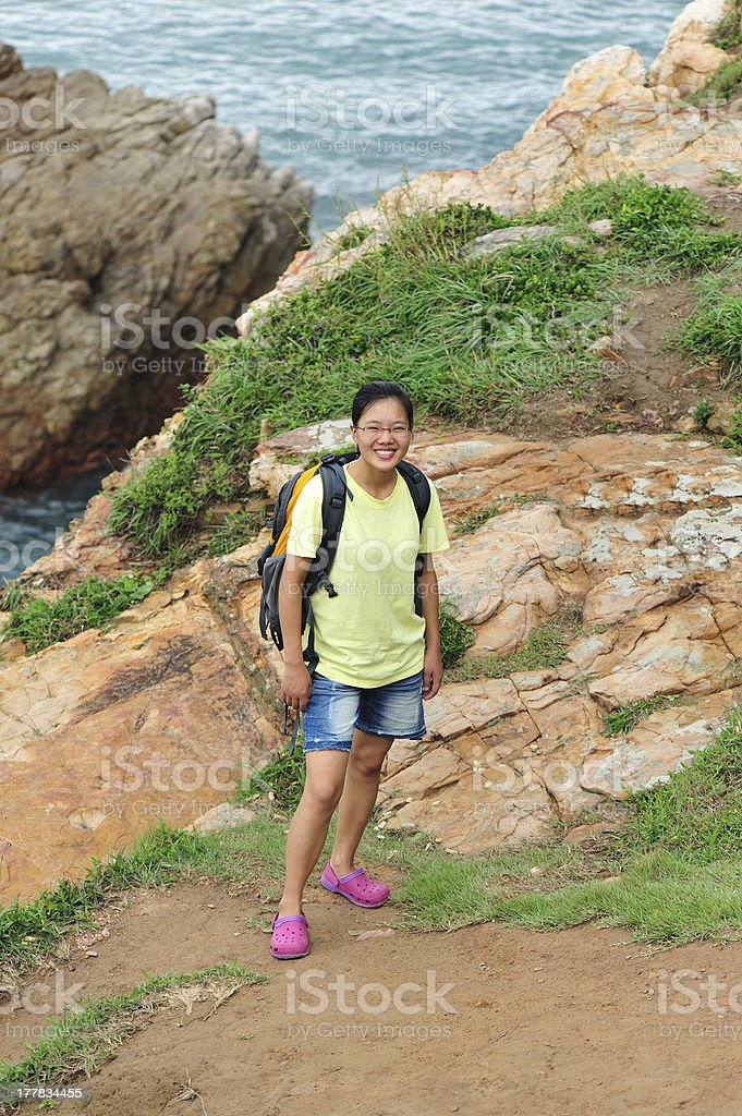 woman hiker stand at extrusive rock seaside stock photo