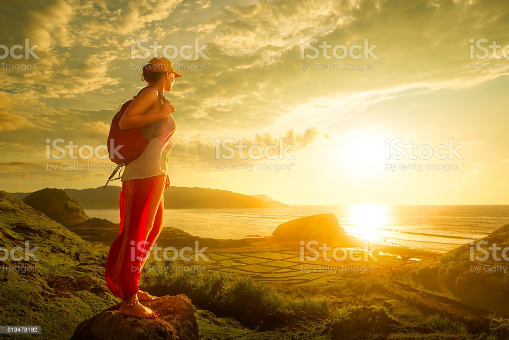 Woman hiker standing on top and enjoying sunset over sea. stock photo