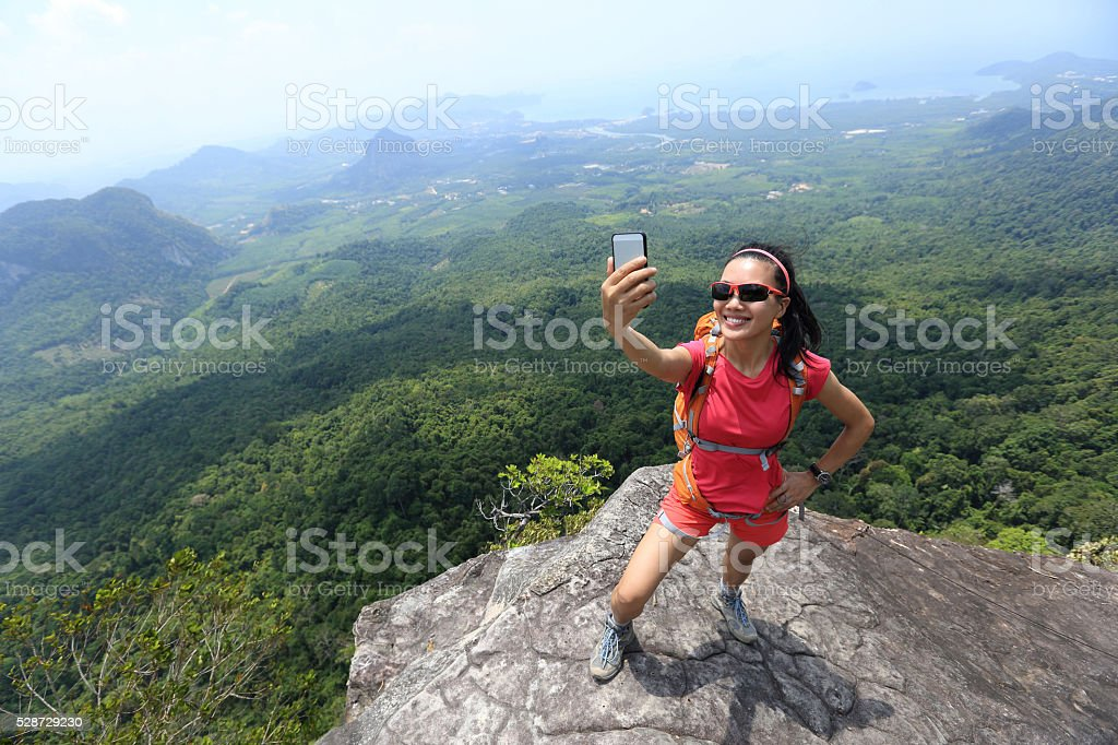 woman hiker use smartphone taking self photo stock photo