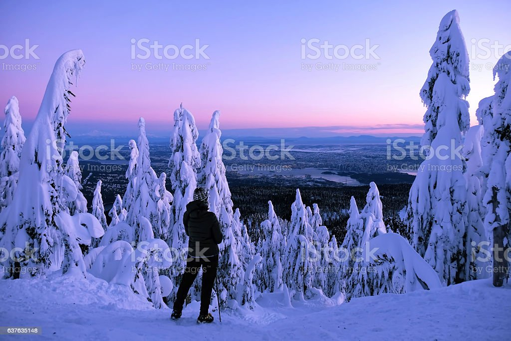 Woman hiker watching sunset from mountain top. stock photo