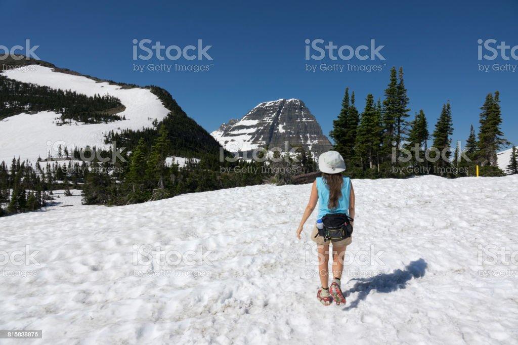Woman hikes Glacier National Park Logan Pass snowfield Bearhat Mountain Montana stock photo