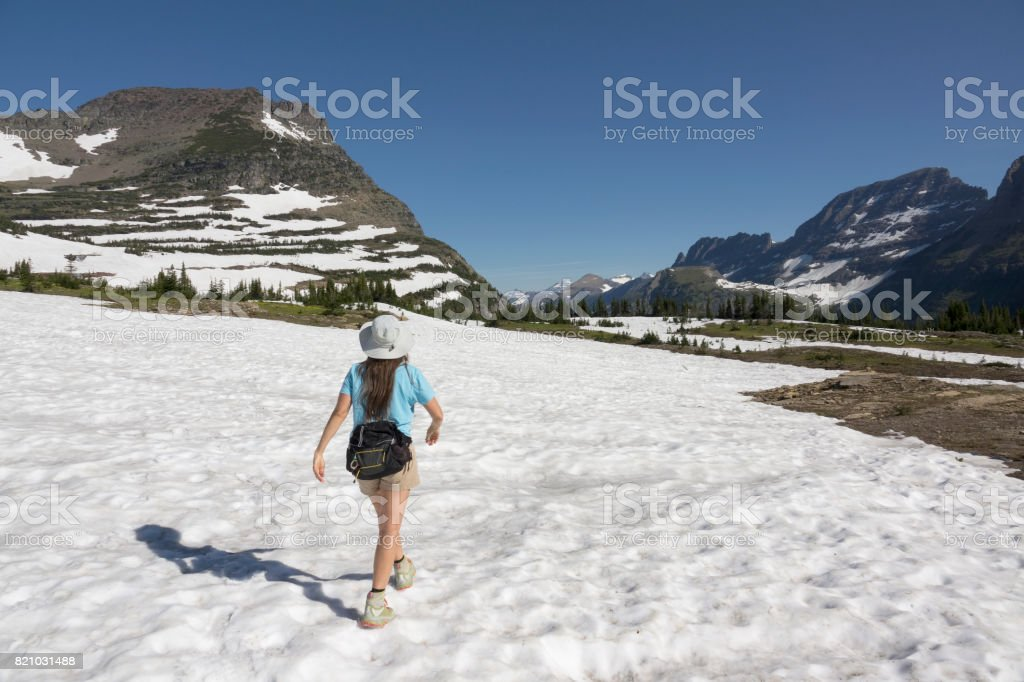 Woman hikes Glacier National Park Logan Pass snowfield Garden Wall Montana stock photo