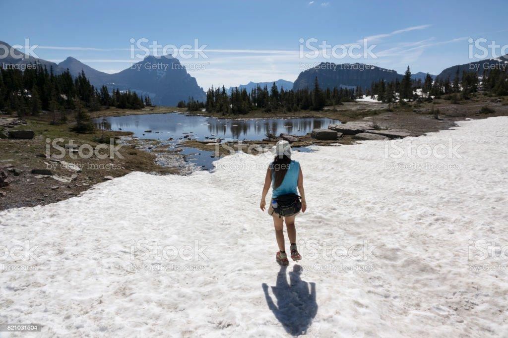 Woman hikes Glacier National Park Logan Pass snowfield lake Montana stock photo