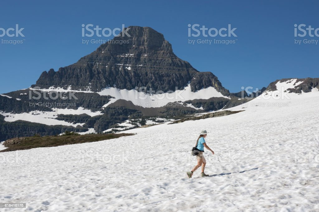 Woman hikes Glacier National Park Logan Pass snowfield Reynolds Mountain Montana stock photo