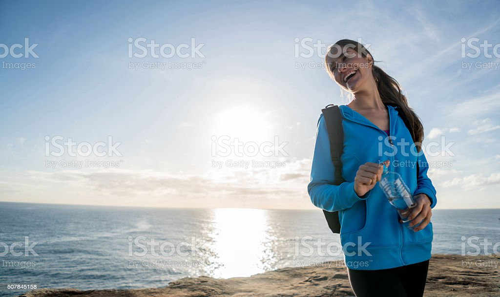 Woman hiking and holding a bottle of water stock photo