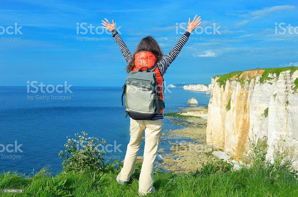 Woman hiking and looking at beautiful sea and rocks view stock photo