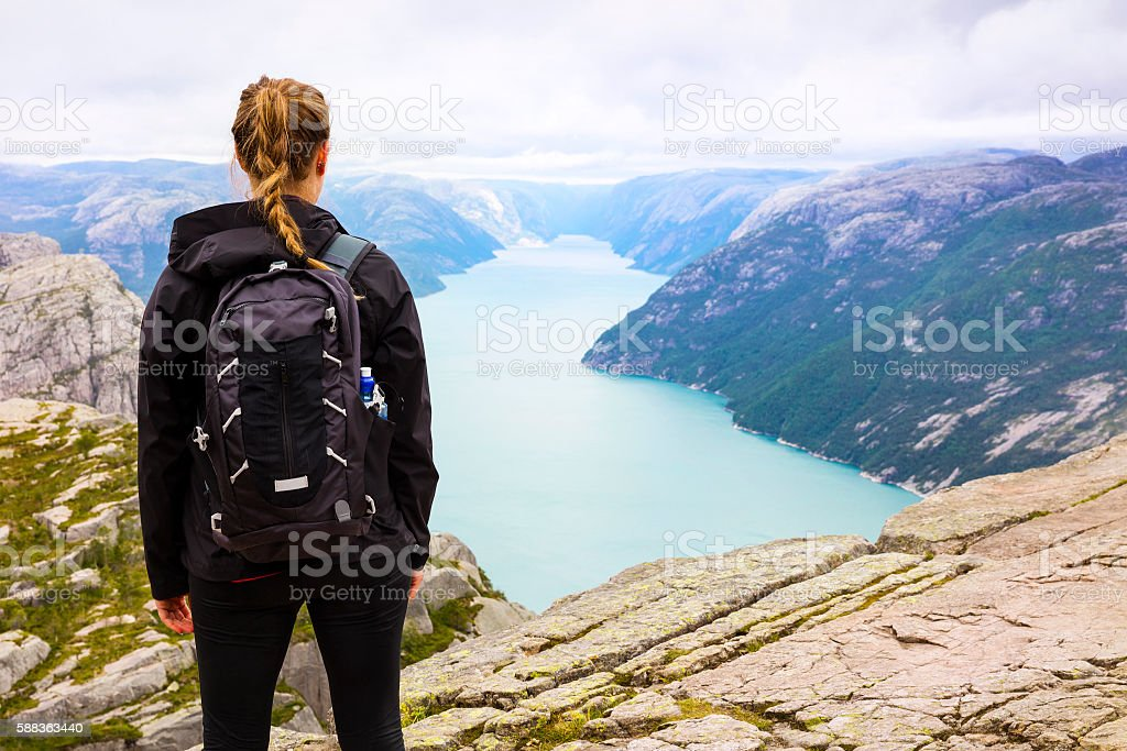 Woman hiking at the Preikestolen cliff in lysefjorden Norway stock photo