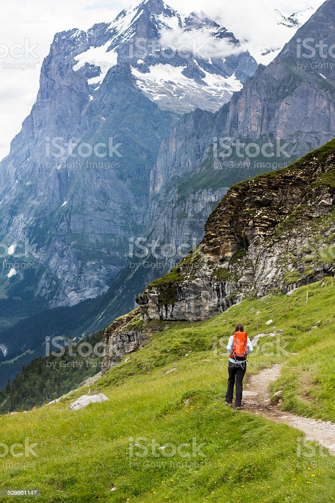 Woman Hiking below Cliff stock photo