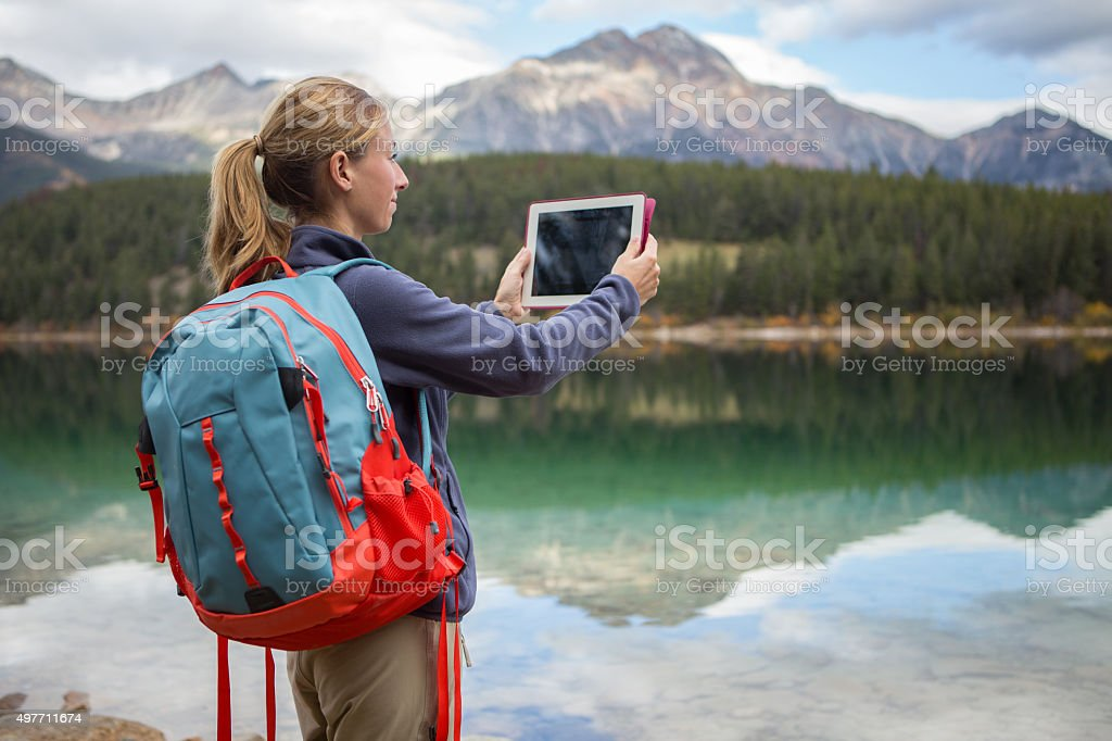 Woman hiking by the lake takes picture using digital tablet stock photo