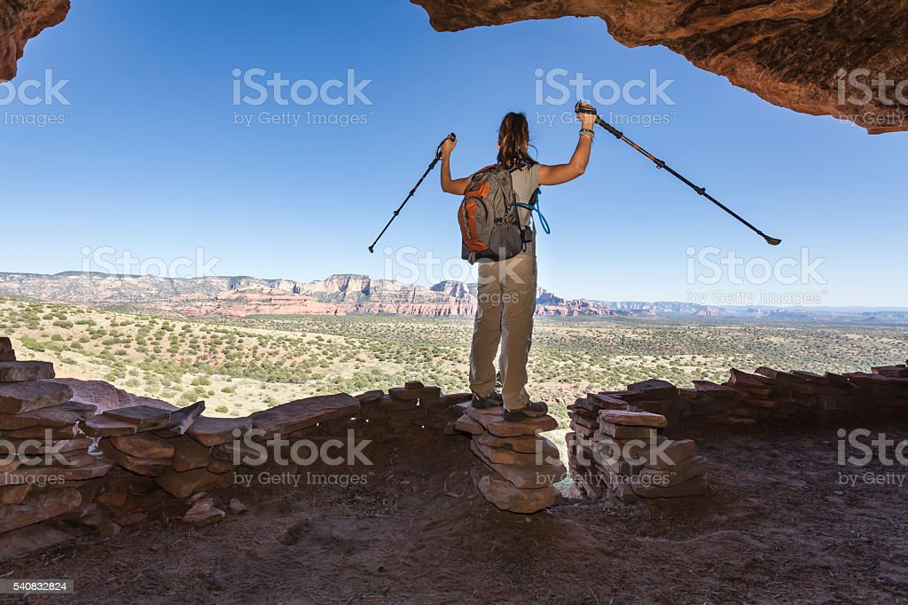 Woman Hiking Celebrates After Reaching a Cave stock photo