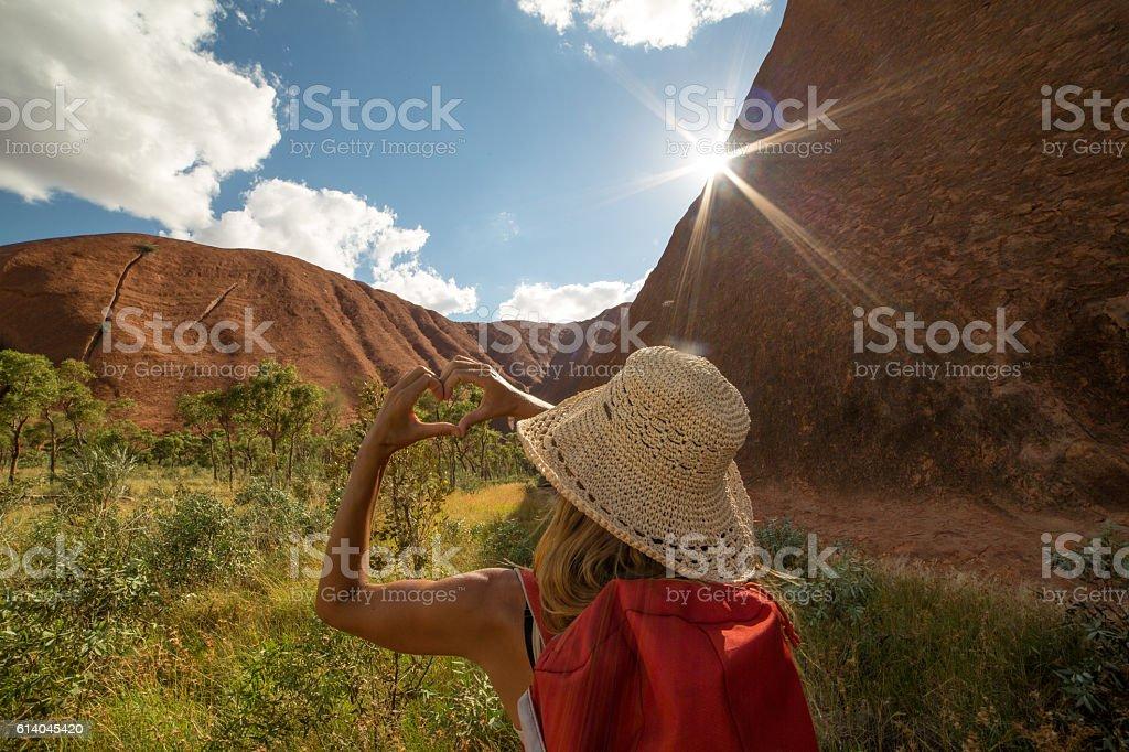 Woman hiking frames landscape into heart shape stock photo