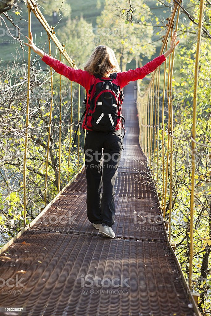 Woman hiking in suspension bridge with outstretched to hands royalty-free stock photo