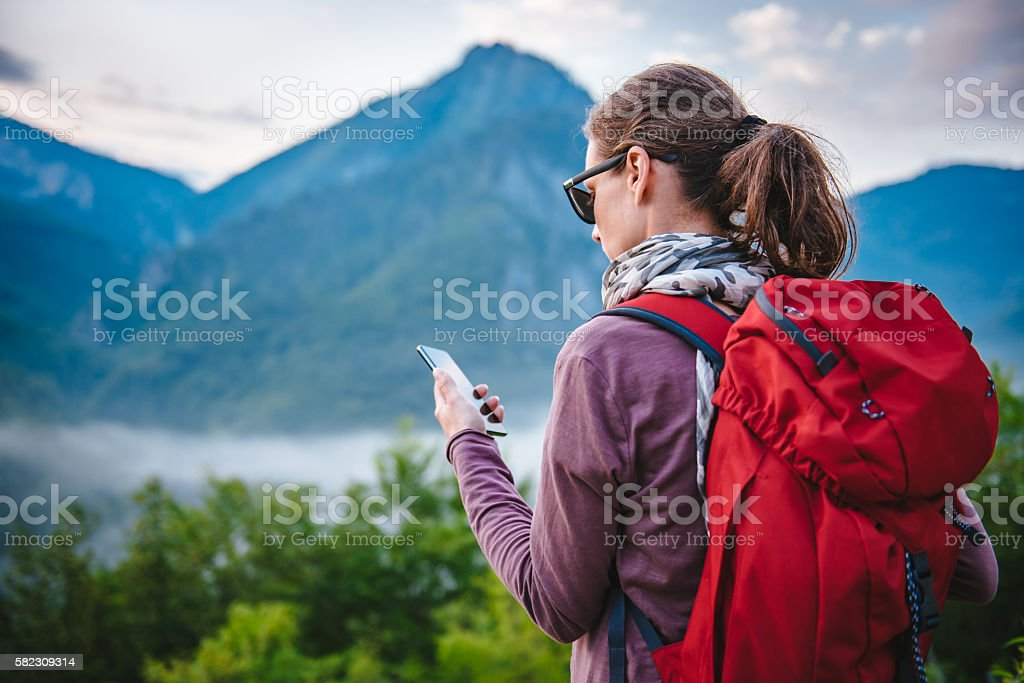 Woman hiking on the mountain and using smart phone stock photo