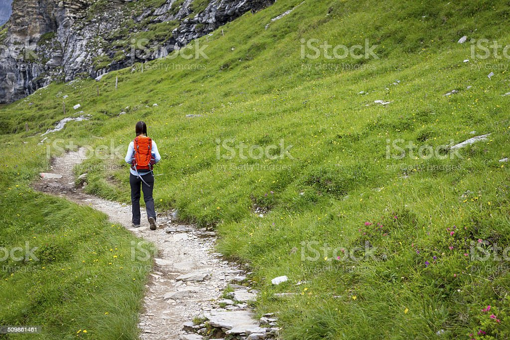 Woman Hiking on Winding Mountain Path stock photo