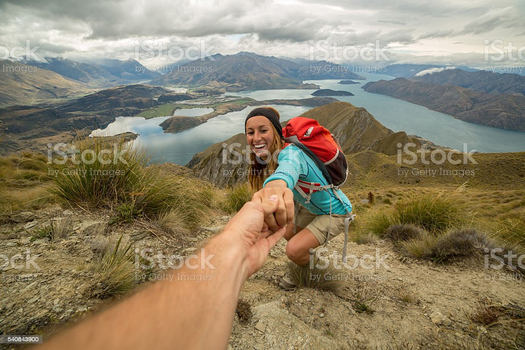 Woman hiking pulls out hand to get assistance from teammate stock photo