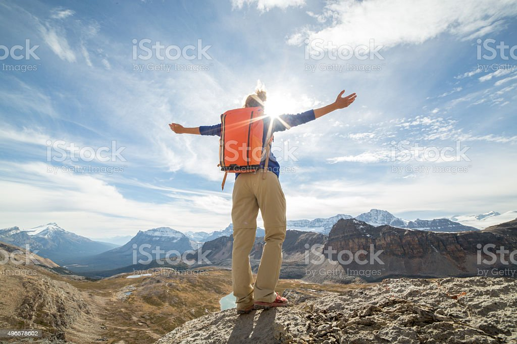 Woman hiking reaches mountain top, arms outstretched stock photo