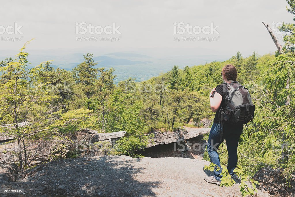 Woman Hiking Stands on Mountain Looking at View New York stock photo