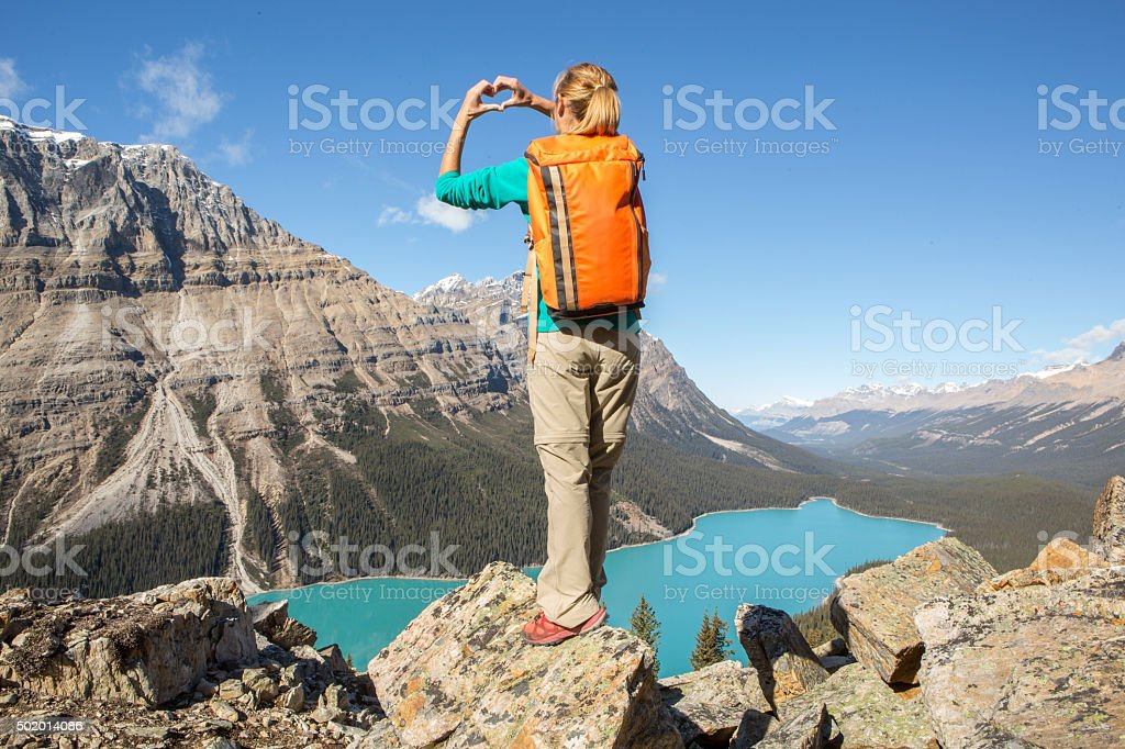 Woman hiking stands on mountain top and makes heart shape stock photo