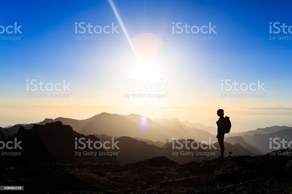 Woman hiking success silhouette in mountains sunset stock photo