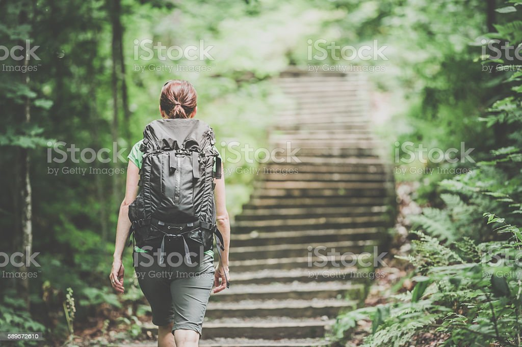 Woman Hiking Trekking with Backpack on Footpath in Forest stock photo