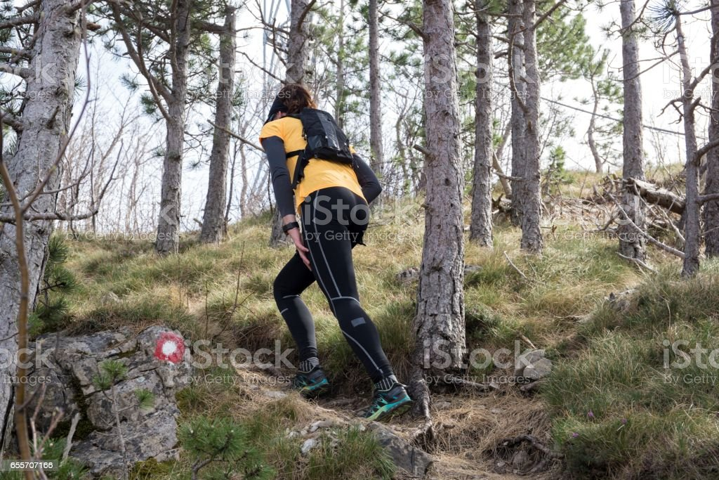 A woman hiking up through a path. National park Paklenica, the part of Velebit; the largest mountain range in Croatia. stock photo